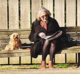 retired woman in park bench with dog